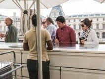 赞助人选择快餐在天窗阳台,巴黎的咖啡馆 免版税库存照片