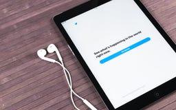 赞成苹果计算机在木桌开头慌张应用主页的iPad和耳机 慌张在网上社会网络和 免版税图库摄影