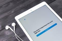 赞成苹果计算机在木桌开头慌张应用主页的iPad和耳机 慌张在网上社会网络 图库摄影