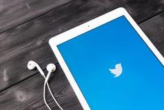 赞成苹果计算机在木桌开头慌张应用的iPad和耳机 慌张在网上社会网络和microblogging 库存照片