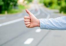 赞许姿态尝试中止汽车路背景 搭车的手势 保证您认识正确的姿态停止汽车 免版税图库摄影