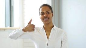 赞许姿态由美国黑人的妇女的在办公室 免版税库存图片