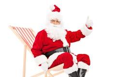 给赞许的圣诞老人供以座位在太阳懒人 库存图片