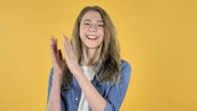 赞许的年轻俏丽的女孩,拍手在黄色背景 股票视频