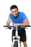 给赞许的有吸引力的体育人骑马登山车训练 库存照片