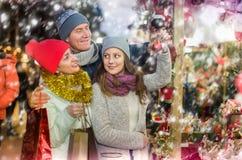 赞赏的家庭加上选择圣诞节12月的青少年的女儿 库存照片