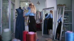 赞赏被缝合的礼服的满意的裁缝 股票录像