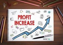 赢利增量,企业概念 笔记本、笔和色的铅笔在一张木桌上 免版税库存图片