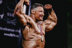 赢取与奖牌的竞争姿势的男性爱好健美者 免版税图库摄影
