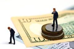 赢取和丢失的商人小雕象 微型模型 现金钞票和硬币 免版税库存照片