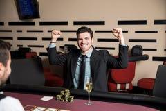 赢取在啤牌的激动的人 免版税库存图片