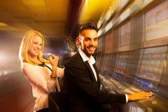 赢取在老虎机的年轻夫妇在赌博娱乐场 免版税库存照片