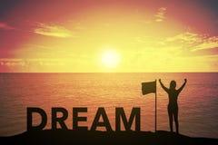 赢取的成功妇女剪影站立和举手的日落或日出的在与文本梦想的旗子附近 免版税库存图片