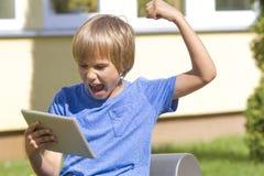 赢比赛 伸手可及的距离目标 非常看起来愉快的男孩冲击与在片剂个人计算机的张的嘴 室外 流动技术休闲骗局 免版税库存照片