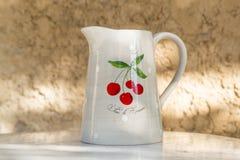 赤土陶器水罐用樱桃 免版税库存照片