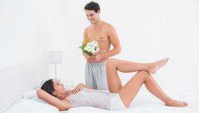 赤裸上身的人提供的花 免版税库存图片