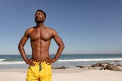 赤裸上身的人用在臀部和眼睛的手在阳光下结束了站立在海滩 免版税库存图片