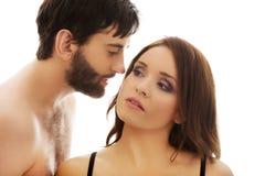 赤裸上身的人耳语对woman& x27; s耳朵 免版税库存照片