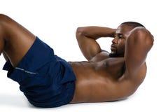 赤裸上身的男性运动员实践的仰卧起坐 免版税库存图片
