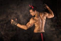 赤裸上身的肌肉男性爱好健美者穿戴了与恶魔服装 免版税库存图片