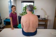 赤裸上身的资深男性患者背面图坐看微笑的女性治疗师的床 库存照片
