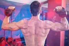 赤裸上身的运动员举的kettlebells背面图  免版税库存图片