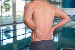 赤裸上身的适合游泳者的中间部分以由水池的后背疼痛 图库摄影