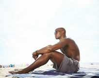 赤裸上身的年轻人坐看的海滩  免版税库存图片