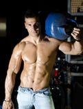 赤裸上身肌肉年轻的人,在肩膀的运载的汽油箱 免版税库存照片