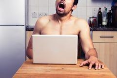 年轻赤裸人观看的色情在他的厨房里 免版税库存照片