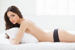 赤裸秀丽。说谎在她的女用贴身内衣裤的美丽的少妇为 免版税库存照片