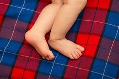 赤裸婴孩腿新出生在格子呢 方格的背景 的treadled 库存照片