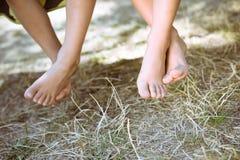 赤足两条儿童腿特写镜头在晴朗 免版税库存照片