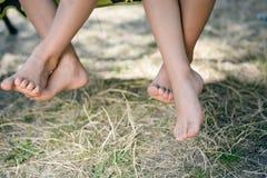 赤足两条儿童腿的室外图片 愉快的孩子特写镜头坐晴朗的乡下 免版税图库摄影