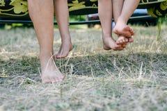 赤足两条儿童腿的室外图片 愉快的孩子特写镜头坐晴朗的乡下 免版税库存图片