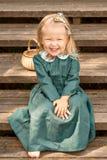 赤足和笑坐木台阶的葡萄酒减速火箭的亚麻制礼服的小女孩在有柳条筐的公园 库存图片