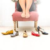 赤足椅子的妇女未定关于佩带的什么鞋子 免版税库存照片