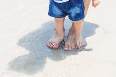 赤足脚爸爸和儿子沙子的在美丽的海滩 免版税图库摄影