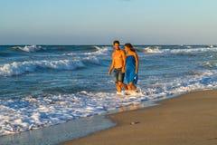 赤足走在一个湿海滩的年轻夫妇在 免版税图库摄影