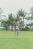 赤足走在一个热带绿色领域的妇女 可视巴厘岛美丽的印度尼西亚海岛kuta人连续形状日落的城镇 努沙Dua公园 库存照片