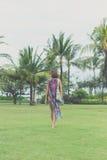 赤足走在一个热带绿色领域的妇女 可视巴厘岛美丽的印度尼西亚海岛kuta人连续形状日落的城镇 努沙Dua公园 免版税库存图片