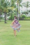 赤足走在一个热带绿色领域的妇女 可视巴厘岛美丽的印度尼西亚海岛kuta人连续形状日落的城镇 努沙Dua公园 库存图片