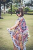 赤足走在一个热带绿色领域的妇女 可视巴厘岛美丽的印度尼西亚海岛kuta人连续形状日落的城镇 努沙Dua公园 免版税库存照片
