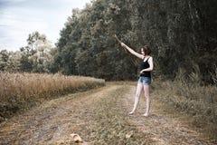 赤足走在地面路通过领域和森林,夏天的概念和旅行的女孩 库存图片