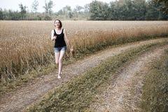 赤足走在地面路通过领域和森林,夏天的概念和旅行的女孩 免版税库存照片