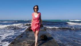 赤足走在往照相机的海码头的年轻可爱的妇女在红色礼服和太阳镜 击中p的风雨如磐的波浪 股票录像