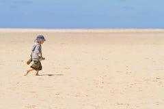 赤足走在沙子的男孩子项 免版税图库摄影