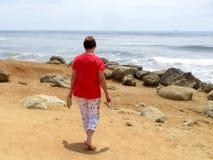 赤足走在海洋海滩的妇女 免版税库存图片