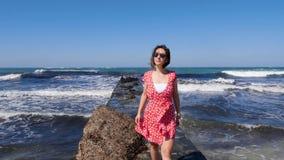 赤足走在海码头的年轻微笑的愉快的妇女 在风的红色礼服拍动 击中海码头的波浪 股票视频