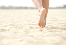 赤足走在海滩的妇女 免版税库存照片